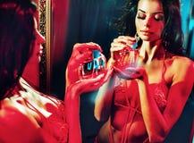 Sensual woman holding a perfume bottle Royalty Free Stock Photos
