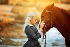 Sensual woman hugging a brown horse in the sunlight royalty free stock images