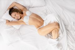 Sensual woman laying in bed. Above view of pretty female in peignoir lying on bed with smile Royalty Free Stock Photo