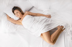 Sensual woman laying in bed. Above view of pretty female in peignoir lying on bed with smile. Above view Stock Photo