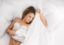 Sensual woman laying in bed. Above view of pretty female in peignoir lying on bed with smile. Above view Royalty Free Stock Images