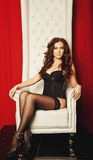 Sensual woman in lingerie sitting on throne Stock Image