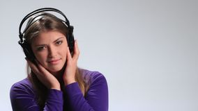 Sensual woman listening music in headphones stock video footage