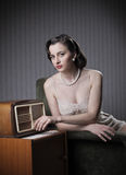 Sensual woman listening music on old radio Stock Photography