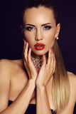 Sensual woman with long blond hair and bright makeup. Fashion studio portrait of beautiful sensual woman with long blond hair and bright makeup Stock Photography