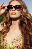Sensual woman with long red hair in luxurious sequin dress with sunglasses Royalty Free Stock Photos