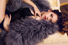 Sensual woman with luxurious curly hair wearing elegant fur coat Stock Photos