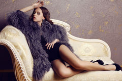 Sensual woman with luxurious curly hair wearing elegant fur coat Stock Photo