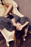 Sensual woman with luxurious curly hair wearing elegant fur coat Stock Photography