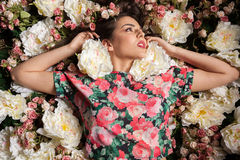 Sensual woman lying down on flowers Stock Images