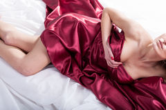 Sensual woman lying in red bedding Stock Photos