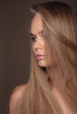 Sensual woman model with shiny straight long blond hair. Young girl with long hair on a beige background. Profile Royalty Free Stock Photography