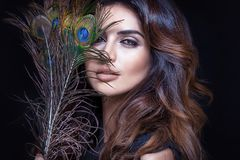 Sensual woman with peacock feather. Beauty portrait of attractive woman with glamour makeup and peacock feather Royalty Free Stock Image