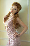 Sensual woman in pearls. Sensual red-haired woman in pearls and lace dress, standing by the wall Royalty Free Stock Photo