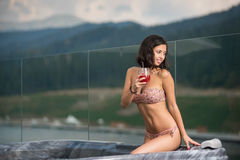 Sensual woman with perfect body in bikini sitting at the Jacuzzi with cocktail and looking away Stock Photos