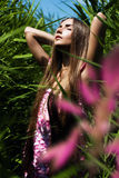 Sensual woman in pink dress with flower Stock Photos