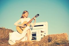 Sensual woman play guitar on wooden bench. Albino girl hold acoustic guitar, string instrument. Fashion musician in. White dress on sunny nature. Woman stock photo