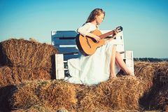 Sensual woman play guitar on wooden bench. Woman guitarist perform music concert. Albino girl hold acoustic guitar. String instrument. Fashion musician in royalty free stock photo