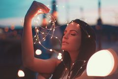 Sensual woman playing with fairy lights outdoors teal and orange royalty free stock images