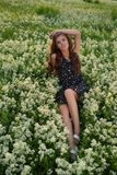 Sensual woman posing outdoors sitting on flowers. stock image