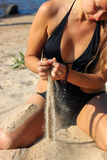 Sensual woman pouring sand on beach Stock Images
