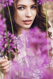 Sensual woman among purple flowers Stock Photos