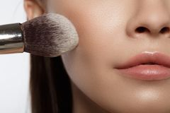 Sensual woman putting on blush on face. Close up of brush applying powder on female cheek. Beauty concept Stock Photo