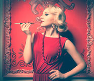 Sensual woman in red dress smoking Stock Photography