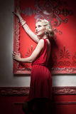 Sensual woman in red dress vintage room Stock Photo