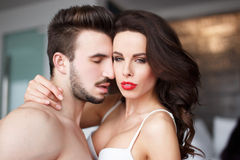 Sensual woman with red lips in hotel room with young lover Royalty Free Stock Image