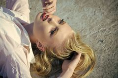 Sensual woman with red sexy lips on makeup face outdoor. Beauty, look concept. Skincare, skin, make up. Girl with long blond healthy hair lie on concrete Royalty Free Stock Images