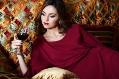 Woman with a red wine glass on a magnificent sofa Stock Photography