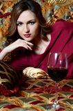 Woman with a red wine glass on a magnificent sofa Stock Image