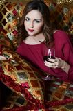 Woman with a red wine glass on a magnificent sofa Royalty Free Stock Photo