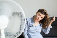Sensual woman refreshing in front of cooling fan. Sensual woman refreshing in front of a cooling fan stock photos