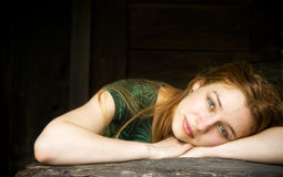 Sensual woman relaxing in front of wooden barn. Beautiful young woman relaxing in front of a wooden house Stock Image