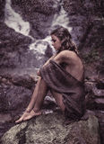 Sensual woman resting near to the waterfall Royalty Free Stock Photography