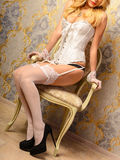 Sensual woman with sexy legs in stockings sit on chair Royalty Free Stock Image