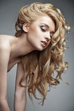 Sensual woman with shiny curly long blond hair. Well-being & spa. Sensual woman model with shiny curly long blond hair. Health, beauty, wellness, haircare Royalty Free Stock Photo