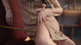 Sensual woman sits in an armchair and runs her hand over the dress, woman in night dress, dress embroidered with stock video footage