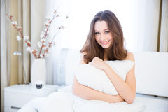 Sensual woman sitting on bed and hugging pillow Royalty Free Stock Photos