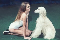 Sensual woman smile to dog friend. Happy woman with cute pet. Fashion girl in bodysuit with domestic animal. Beauty royalty free stock image