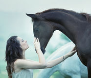 Sensual woman stroking a horse. Sensual woman stroking a wild horse Royalty Free Stock Images