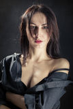 Sensual woman undressing. Sensual woman with bare shoulder on black background Stock Images