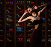 Sensual Woman in Wardrobe with Plenty of Footwear. Pretty Dreamy Woman  with  Footgear Stock Photography