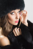 Sensual woman wearing black fur and pearls Royalty Free Stock Images