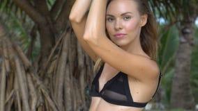 Sensual woman wearing black swimwear on a beautiful summer day between palm trees stock video