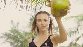 Sensual woman wearing black swimwear on a beautiful summer day between palm trees stock footage