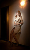 Sensual woman wearing a coat posing provocatively laying against a wall. Young model posing in front of a wall lighted from upper Stock Photos