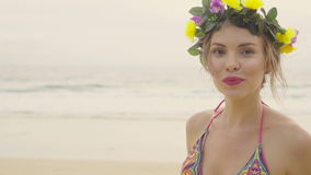 Sensual woman wearing colourful swimwear and wreath on a beautiful summer day at the beach stock video